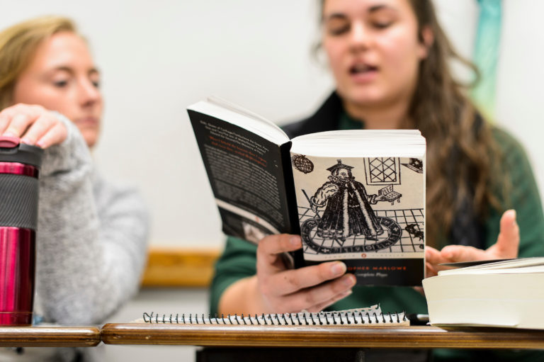 Two students discuss a book in a literature class.