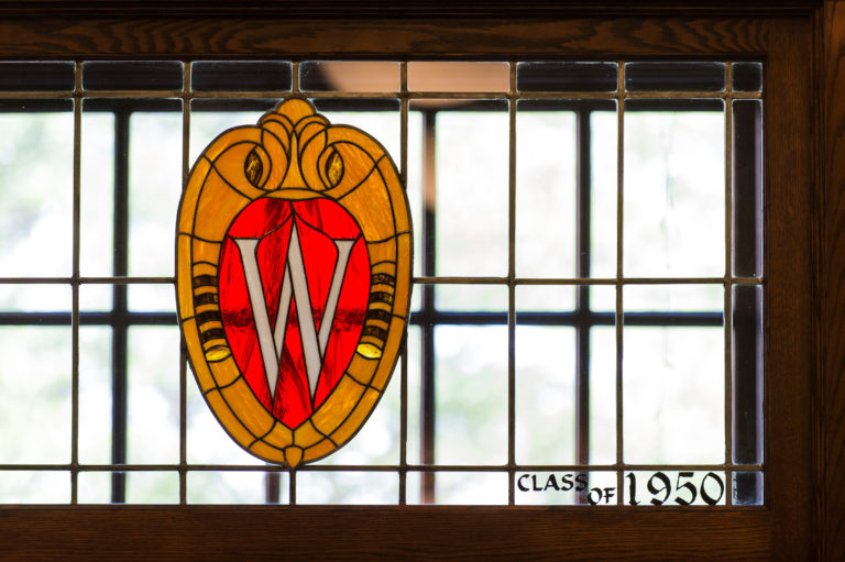 """A window has a stained-glass design of the UW-Madison """"W"""" crest."""