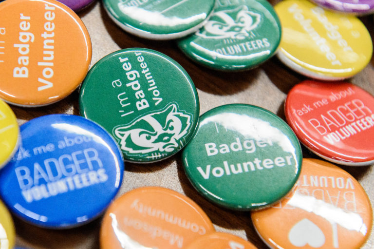 Pin badges for Badger Volunteers are displayed on a table.