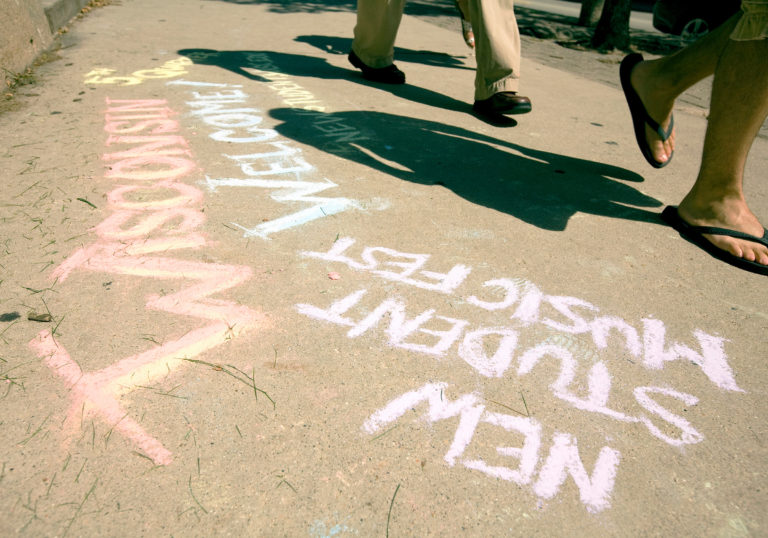Pedestrians walk past a sidewalk-chalk message associated with the Wisconsin Welcome program.